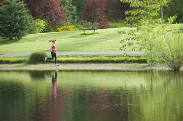 Jogger running near park pond