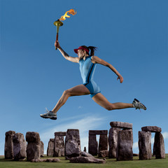 Athlete running with Olympic torch near Stonehenge