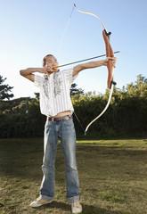 Mixed race archer aiming bow and arrow