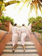 Caucasian couple in robes walking up stairs