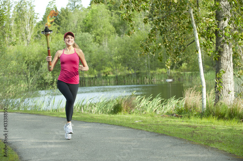 Caucasian athlete running with Olympic torch on park path