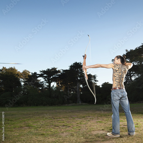 Mixed race archer shooting arrow in field