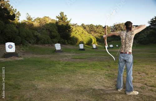 Mixed race archer aiming bow and arrow at target
