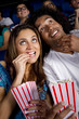 Hispanic couple enjoying popcorn in movie theater