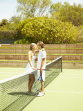 Caucasian couple playing tennis and hugging