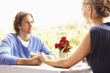 Glamorous Caucasian couple holding hands in restaurant
