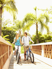 Caucasian couple riding bikes over bridge