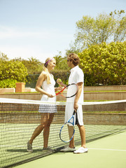 Caucasian couple playing tennis