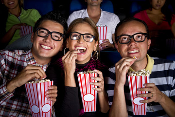 Hispanic friends enjoying popcorn at movie theater