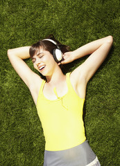 Caucasian teenager laying in grass listening to headphones