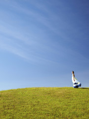 Caucasian teenager in dress standing on hill