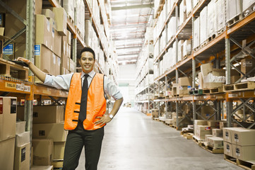 Manager standing in warehouse aisle