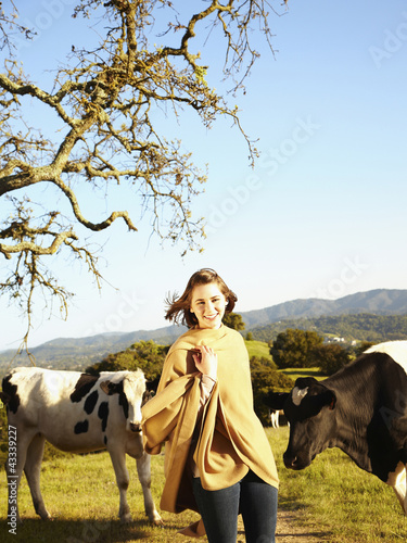Caucasian teenager standing with cows