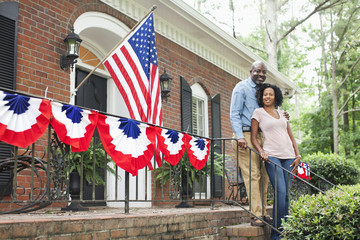 African American couple standing on front stoop of festive house
