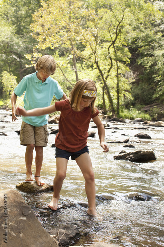 Caucasian brother and sister standing on rocks in stream