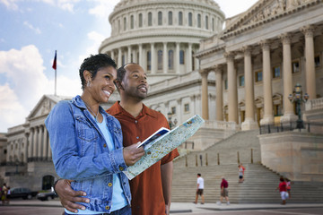 Black couple sightseeing with map