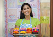 Hispanic woman holding tray of cupcakes