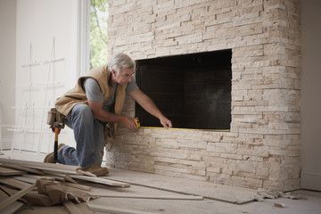 Caucasian carpenter measuring fireplace