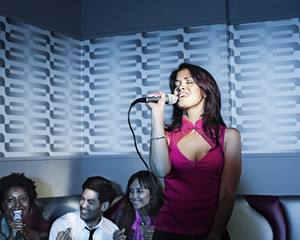 Woman singing karaoke in nightclub