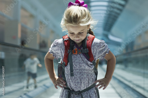 Caucasian girl riding on airport moving walkway