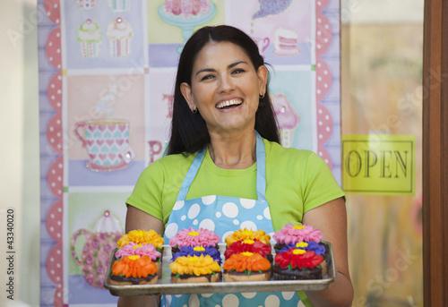 Hispanic woman holding tray of cupcakes