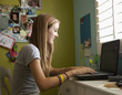 Mixed race teenager using laptop in bedroom