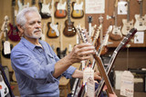 Hispanic craftsman looking at guitars in shop