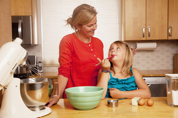 Caucasian woman baking with daughter in kitchen