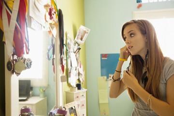 Mixed race teenager looking in bedroom mirror