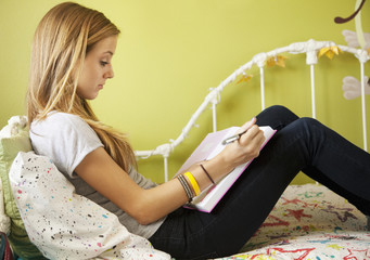 Mixed race teenager sitting on bed doing homework
