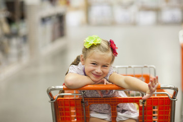 Caucasian girl riding in shopping cart