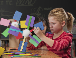 Children making paper wind turbines in classroom