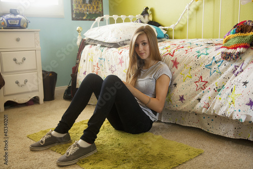 Mixed race teenager sitting on bedroom floor