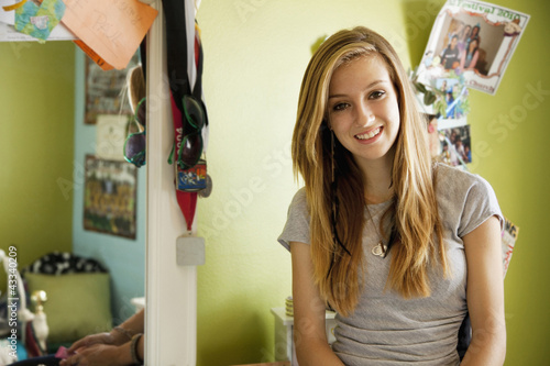 Smiling mixed race teenager in bedroom