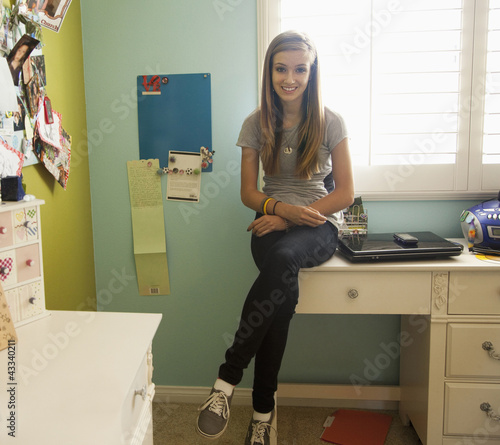 Mixed race teenager sitting on desk in bedroom
