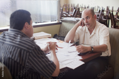 Caucasian restaurant owner working with co-worker in booth