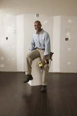 African American man holding cordless drill in unfinished room