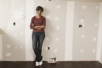 Mixed race woman leaning on wall in unfinished room
