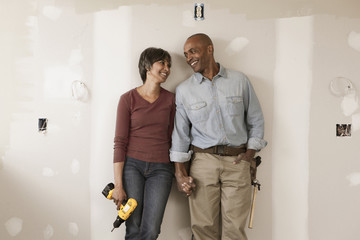 Couple holding hands in unfinished room