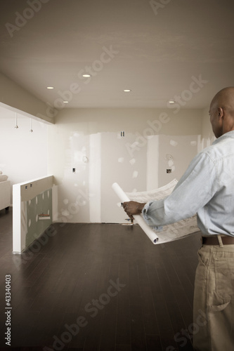 African American man standing in unfinished room with blueprints