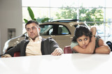Frustrated couple sitting in car showroom