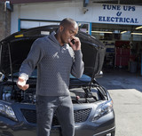 Black man talking on cell phone in auto repair show