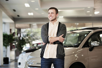 Caucasian man standing in car showroom