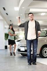 Proud man holding keys to new car in showroom