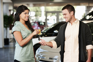 Woman handing man keys to new car in showroom