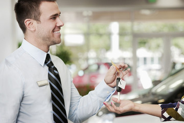 Man handing woman keys to new car in showroom