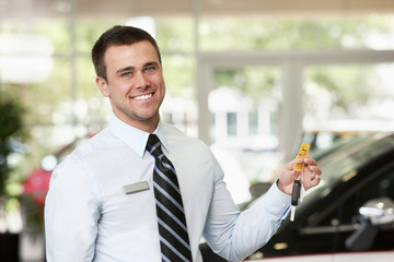 Caucasian man holding keys to new car in showroom