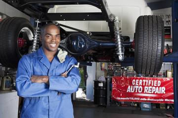 Black mechanic working on car