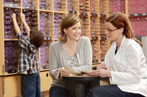 Optician helping customer select eyeglasses