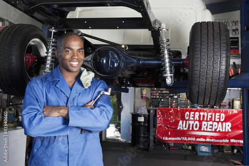 Black mechanic working on car